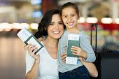 beautiful mother and daughter holding passports and boarding pass at airport poster