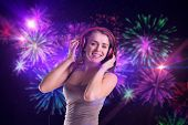 Pretty girl listening to music against digitally generated bright firework design poster