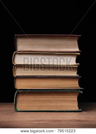 Stack of hardcover books arranged haphazardly viewed from a high angle on a wooden desk or table with copyspace and shadow behind poster