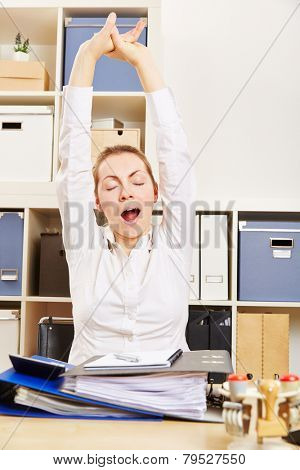 Tired fatigue business woman yawning and stretching in her office