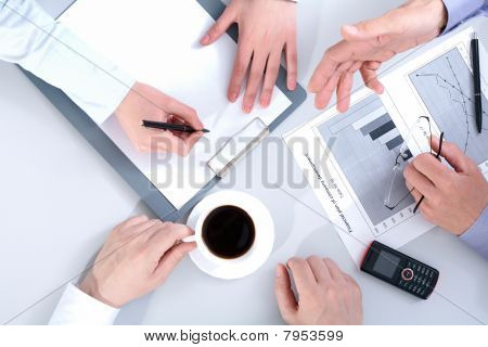 Above view of business people hands working with documents at briefing poster