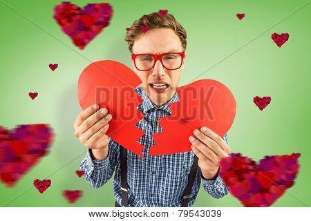 Geeky hipster holding a broken heart against green vignette