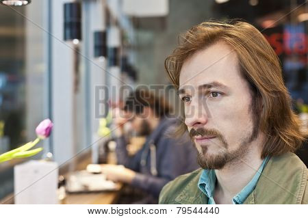 Portrait Of A Pensive And Handsome Young Man In Coffee Shop