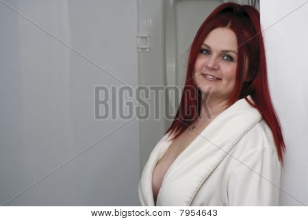 Red hair woman model in white bathrobe standing in bathroom poster