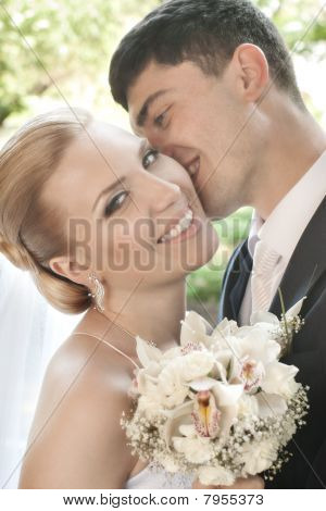 Smiling Bride Kissed In Cheek By Groom