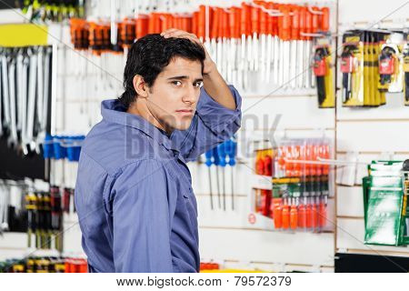 Side view portrait of confused customer with hand on head in hardware shop