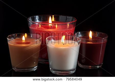 Four of burning candles in glass candle holders on black background.