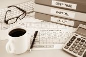 Human resources documents: payroll salary and employee time sheets place on office table with cup of coffee and calculator sepia tone poster