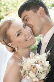 Happy bride being kissed in the cheek by groom with selective focus poster