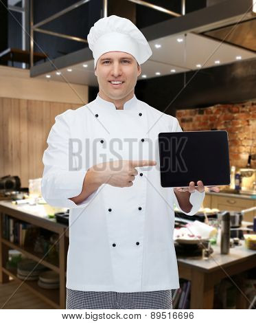 cooking, profession and people concept - happy male chef cook showing tablet pc computer black blank screen over kitchen background
