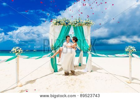 Wedding Ceremony On A Tropical Beach In Blue. Happy Groom And Bride Under The Arch