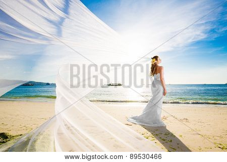 Beautiful Fiancee In White Wedding Dress And Big Long White Train, Stand On Shore Sea At Sunset