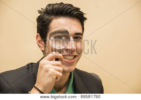 Handsome young man holding a magnifying glass