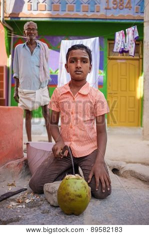 KAMALAPURAM, INDIA - 02 FEBRUARY 2015: Indian boy opening a coconut infront of house in a town close to Hampi
