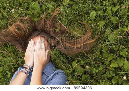 Young cute girl with tousled long hair lying on the green grass covering his face with his hands.