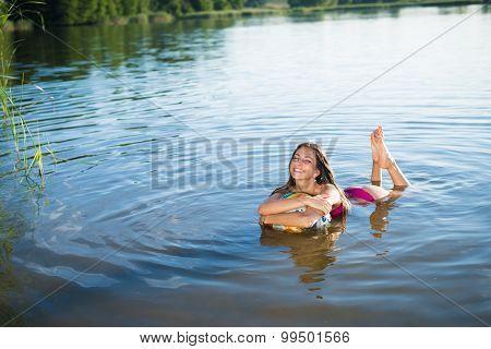 Young happy smiling girl hugging big ball splashing in lake