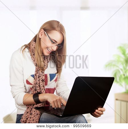 Student girl working at home, preparing to exam in the university, with pleasure typing something on the laptop, gladly receives knowledge on the Internet