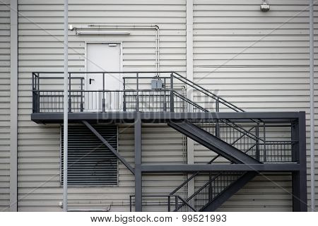 An external staircase made of steel used at a public shopping building also as fire escape. poster
