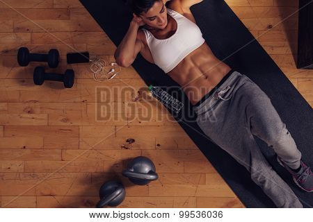 Sporty young woman lying on exercise mat doing sit-ups. Top view of muscular woman doing abs crunches in gym. poster