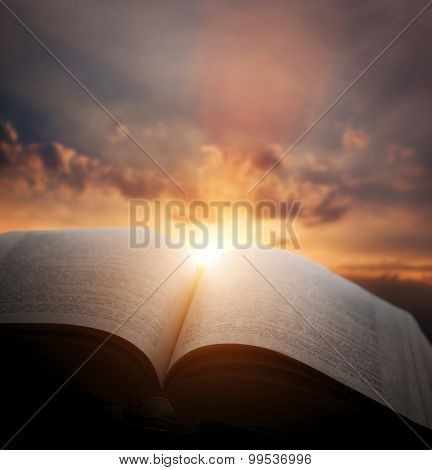 Open old book, light from the sunset sky, heaven. Fantasy, imagination, education, religion concept.