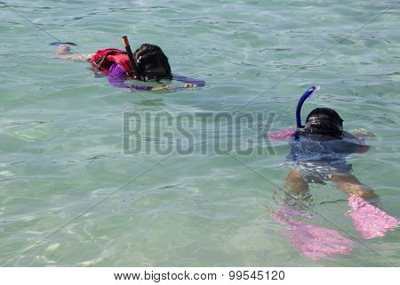 Mother photographing daughter snorkelling