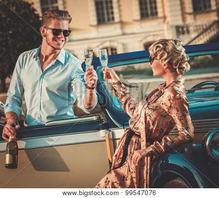 Wealthy couple with champagne near classic convertible  poster