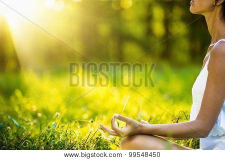 Yoga woman meditating at sunset