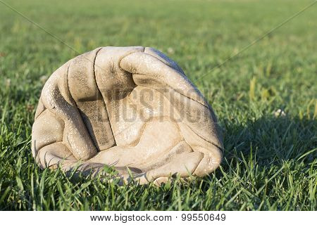 Old Deflated Soccer Ball On The Soccer Field Grass