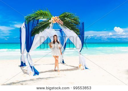 Wedding ceremony on a tropical beach in blue. Happy bride with a wedding bouget under the arch decorated with flowers on the sandy beach. Wedding and honeymoon concept. poster
