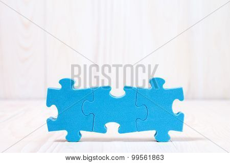 Three Puzzle Pieces On White Wooden Background