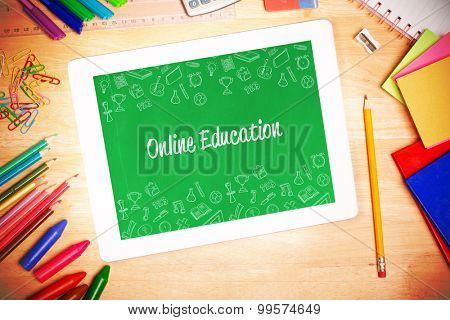The word online education and school wallpaper against students desk with tablet pc
