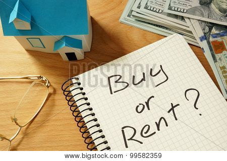 Notepad with buy or rent, home model and dollars.