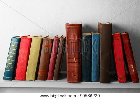 Old books on shelf, close-up, on light wall background poster