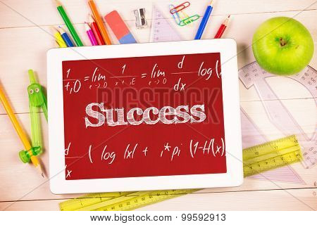 The word success and maths equation against students desk with tablet pc