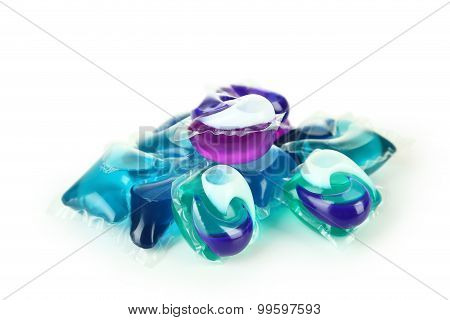Gel capsules with laundry detergent on a white background poster