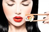 Fashion art portrait of beauty model girl eating Sushi roll, healthy japanese food. Beautiful woman holding chopsticks with sushi. Sexy lady poster