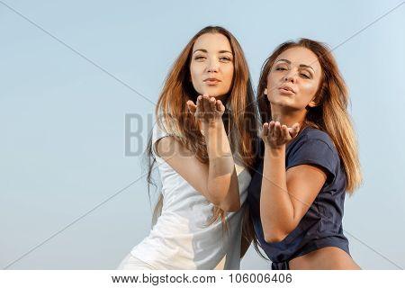Attractive girls sending blow kisses