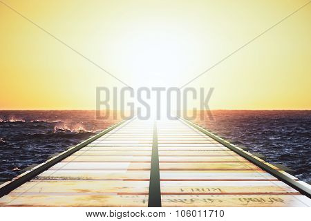 Wooden Bridge In The Ocean Leaving To The Horizon At Sunset