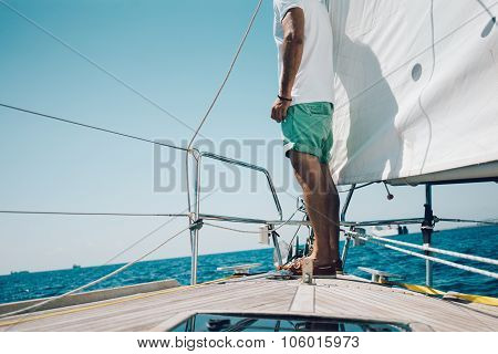 View of young man standing on the nose yacht
