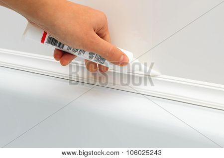 Hands Caulking Bath Tube With White Silicone Glue
