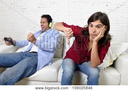 young attractive woman bored angry frustrated and upset while husband or boyfriend plays videogames ignoring her in technology and gaming addiction concept poster