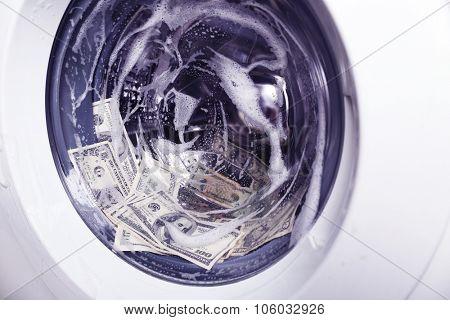 Laundering of money in washing machine, close up