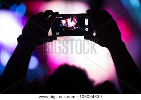 Man takes pictures on his smartphone at concert