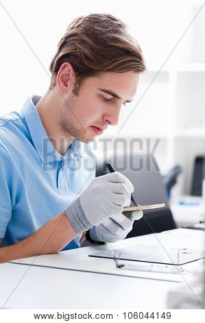 Young man profesional engineer in a phone repair service, fixing a broken smartphone screan.