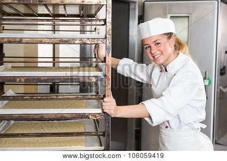 Apprentice Or Worker In Bakery Push Rack With Dough