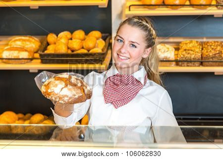 Shopkeeper In Bakery Presenting Loaf Of Bread To Client