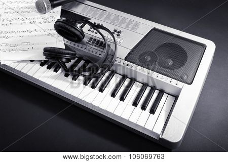 Headphones with music notes and microphone on synthesizer on gray background