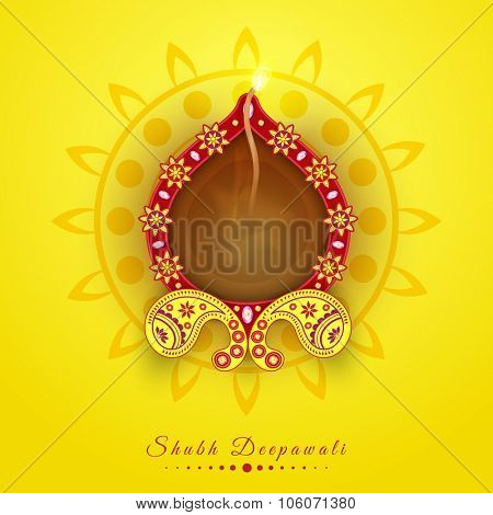 Floral decorated elegant illuminated oil lit lamp on rangoli for Indian Festival of Lights, Happy Diwali celebration.