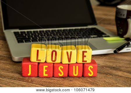 Love Jesus written on a wooden cube in front of a laptop