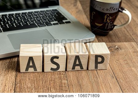 ASAP written on a wooden cube in front of a laptop